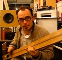 Een foto van een basgitaar van een plank.