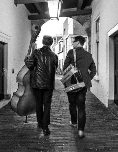 Philip Baumgarten en Peter Pot lopen door een poortje met hun instrumenten.