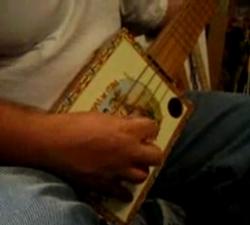A bass guitar made out of a cigar box.