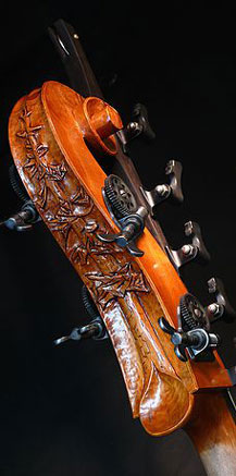 A double bass head with carved plants.