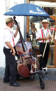 A double bass with wheels and an umbrella.