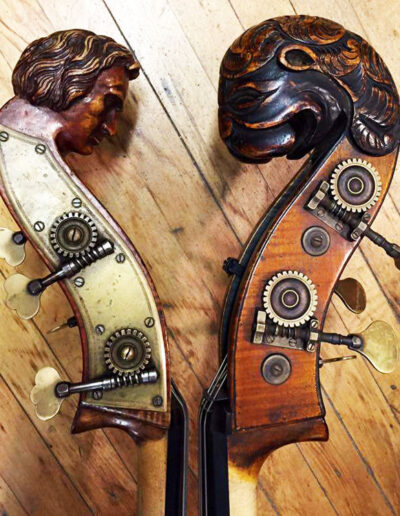 Two carved double bass heads